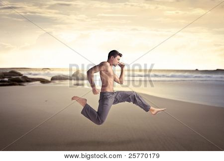Handsome bare-chested man running on a beach