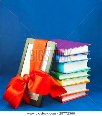 Electronic Book Reader Tied Up With Red Ribbon With Stack Of Books