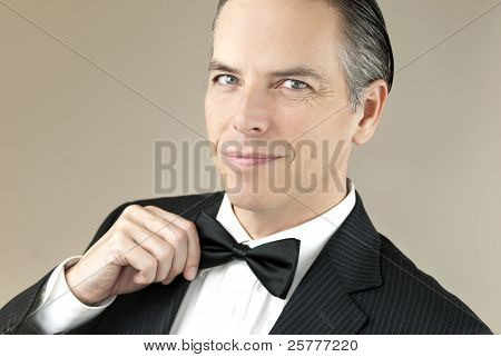 Smiling Gentleman In Tux Adjusts Bowtie With One Hands