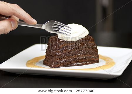 Hand Holding Fork About To Slice Into A Chocolate Marquise With White Chocolate Marscapone And Butte