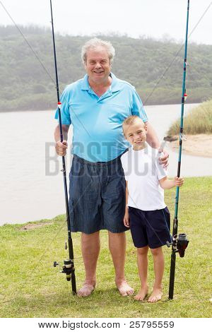 portrait of grandfather and grandson standing by lake with fishing rods