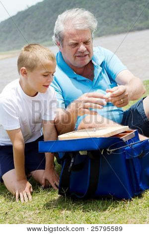 grandfather teaching grandson how to prepare fishing tackles