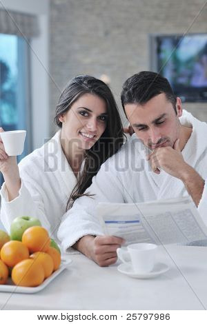 young family couple read newspaper at kitchen in morning with  fresh breakfast  fruits food and coffee drink on table