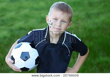 A young boy with painted face and soccer ball.