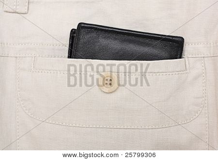 Black wallet in a back pocket in linen trousers.