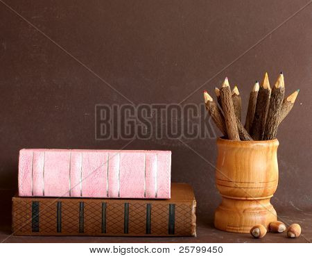 Old school books and wooden pencils on brown background