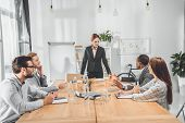 Businesswoman In Formal Suit Standing Against Table And Speaking To Team At Office Space poster