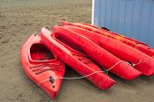 Empty Red Plastic Recreational Kayaks Stacked Up On A Rainy Day. poster