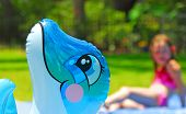 stock photo of floaties  - Poolside Floaty with Girl in Bathing Suit in Background - JPG