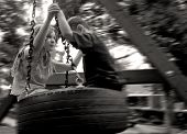 picture of tire swing  - Young Children on Tire Swing with Panning for Motion Blur - JPG