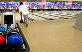 pic of bowling ball  - Stacked bowling balls at festive lanes with bowler in distance - JPG
