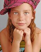 stock photo of newsboy  - Young girl in plaid hat sitting on chair - JPG