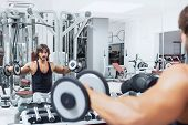 Bodybuilder Lifting Dumbbell Weights In A Gym poster