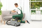Male Janitor Removing Dirt From Sofa With Upholstery Cleaner In Room poster