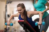 Personal Trainer Helping Pretty Woman With Weight Training Equipment In Gym poster