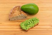 Open Sandwich With Guacamole, Whole Green-skinned Avocado Fruit And Part Of Brown Bread With Sproute poster
