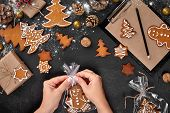 Christmas Gift Gingerbread On Dark Background. Biscuits In Festive Packaging. Woman Is Packaging Chr poster