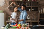 Happy Romantic Couple Dancing In Kitchen While Cooking Together poster