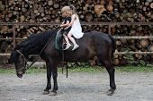 Children Sit In Rider Saddle On Animal Back. Girls Ride On Horse On Summer Day. Friend, Companion, F poster
