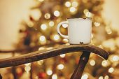Mug With Hot Drink On Old Wooden Chair On Background Of Golden Beautiful Christmas Tree With Lights poster