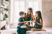 Mom with her two children sitting on the kitchen table and eating candies. Mother with daughter and  poster