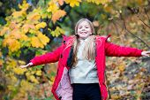 Free And Happy Cutie. Child Blonde Long Hair Walking In Warm Jacket Outdoor. Girl Happy In Red Coat  poster
