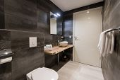 Contemporary Bathroom Tiled With The White And Gray Tiles. There Is A White Sink With Accessories, B poster