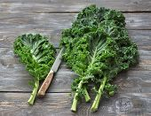 Fresh Green Curly Kale Leaves On A Cutting Board On A Wooden Table. Selective Focus. Rustic Style. H poster