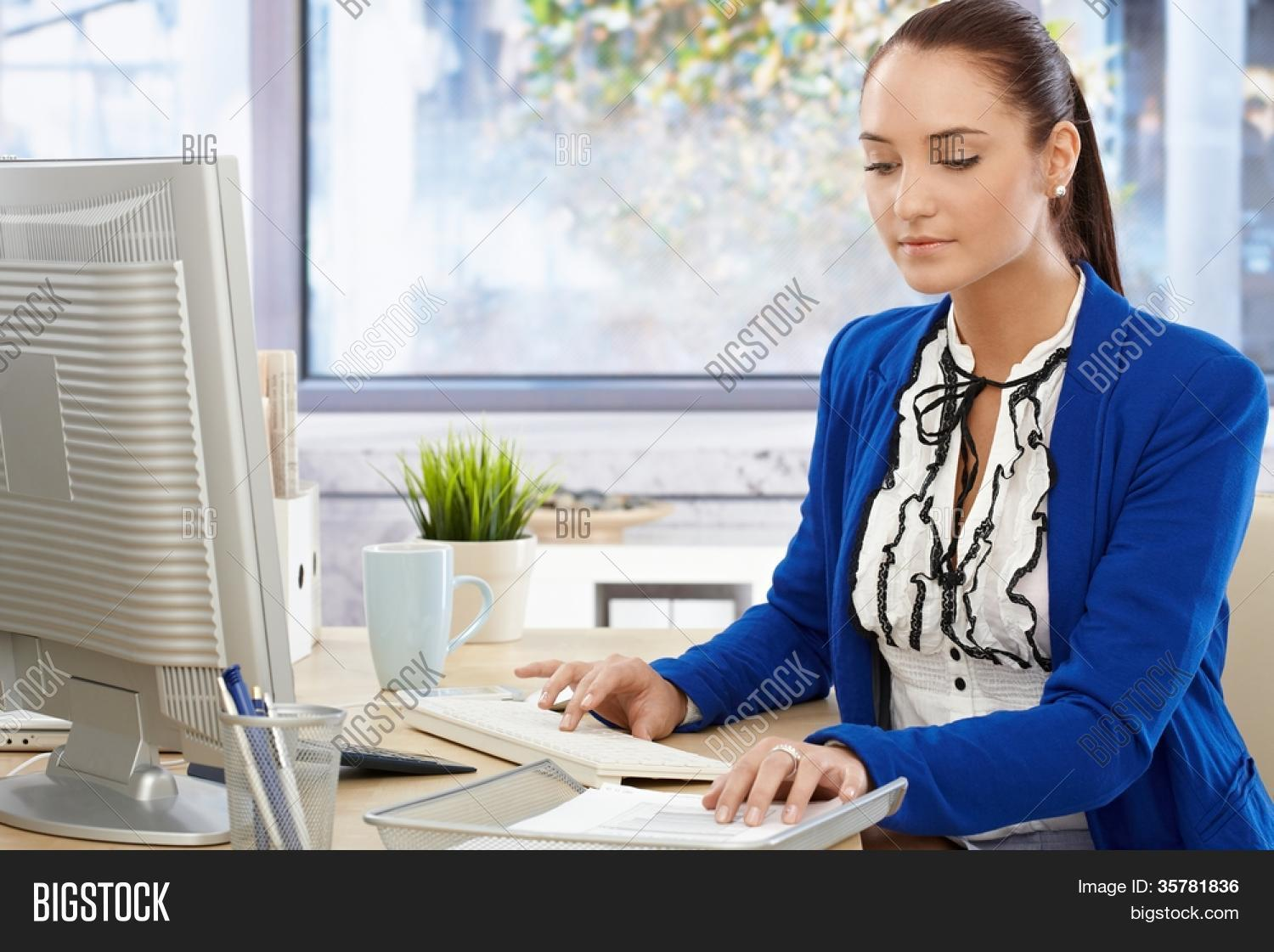 beautiful office girl busy working at bright desk typing on keyboard and checking document beautiful bright office