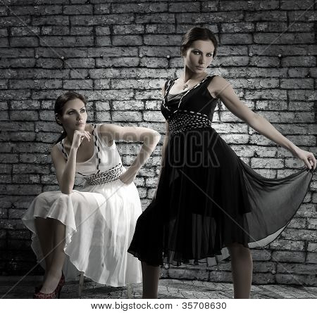 Women Twins In Is Identical-different Dresses Near A Brick Wall