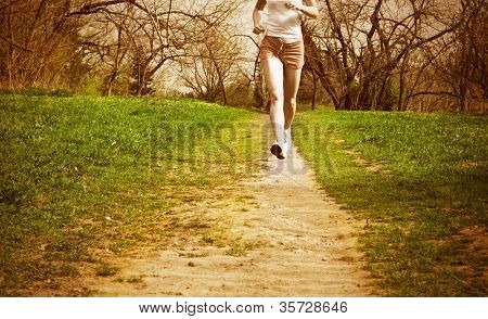 young woman runner in a green forest.