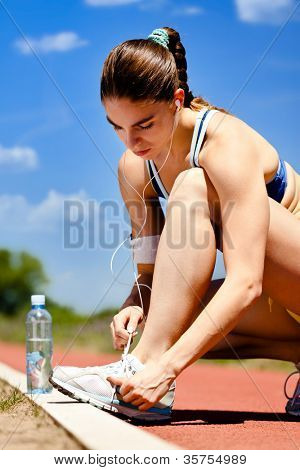 Woman tying her shoelaces before starting her workout