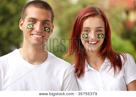 Happy couple with Brazil flags on their cheeks holds Greece flag, outdoor