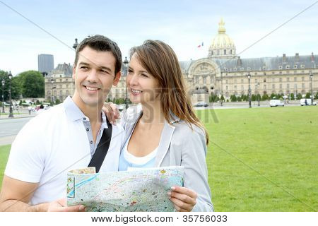 Couple reading tourist map in front of the Invalides building