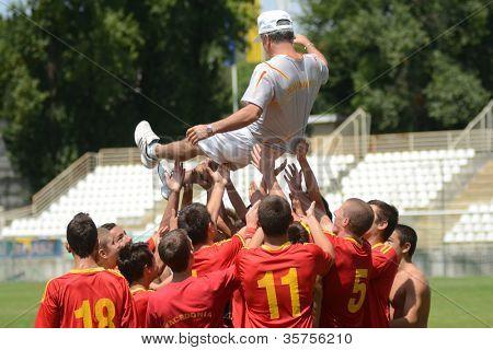 KAPOSVAR, HUNGARY - JULY 21: Macedon players celebrate at the VIII. Youth Football Festival U16 Final Pozo Almonte (yellow) (CHI) vs. FC Makedonija (white) (MKD) July 21, 2012 in Kaposvar, Hungary