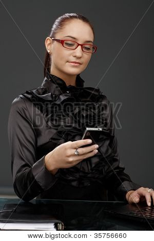 Smiling elegant businesswoman texting on mobile phone, smart shirt and red glasses, using laptop.