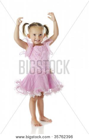 A barefoot preschooler wearing a pink ballerina dress with her arms arched over her head.  On a white background.