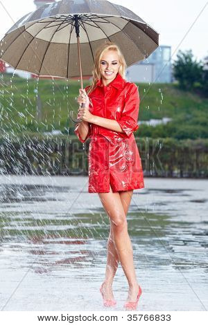 Woman in raincoat smiling as she holds umbrella