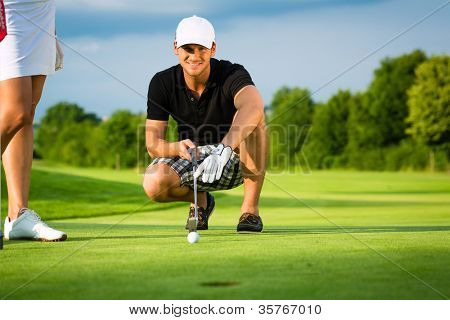 Young golf player on course putting, he aiming for his put shot