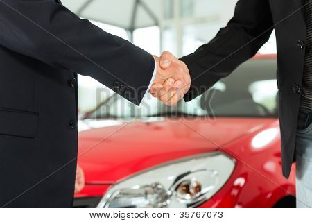 Two men in business suits shaking hands after a successful car purchase