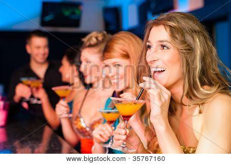 Jóvenes en club o bar bebiendo cócteles y divertirse