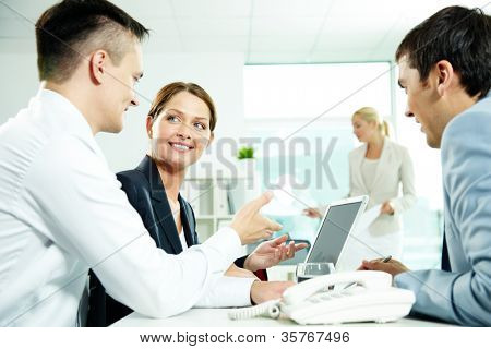 Three business partners interacting at meeting with secretary working on background