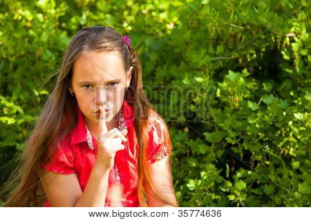 Shh. secret! Beautiful young girl with her finger over her mouth, hushing.