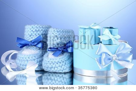beautiful gifts and baby's bootees on blue background