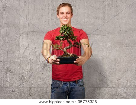 portrait of a young man holding a pot, background