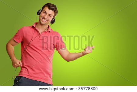 Young man wearing headphones isolated on green background