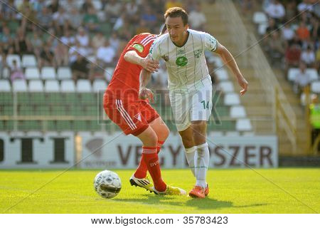 KAPOSVAR, HUNGARY - AUGUST 4: Lorant Olah (in white) in action at a Hungarian National Championship soccer game Kaposvar (white) vs Debrecen (red) August 4, 2012 in Kaposvar, Hungary.