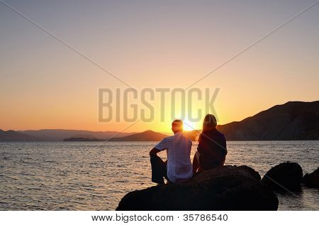 Young girl and boy sitting on a rock by the sea and watching the sunset