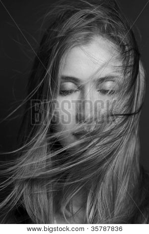 Wellness and spa. Sensual woman model with windswept flying hair on dark background. Shiny long health hairstyle. Beauty and haircare