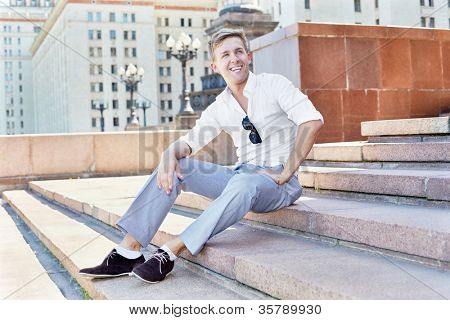 Young man sits on the steps of the architectural complex